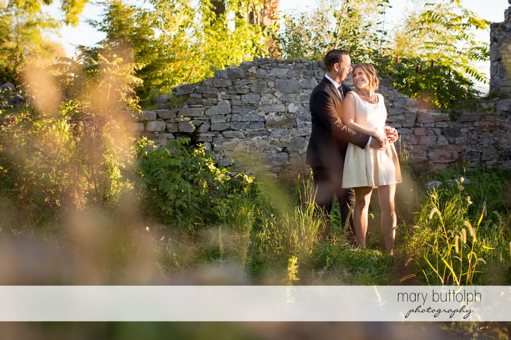 Couple pose in the garden in front of a brick wall at the Inns of Aurora Engagement