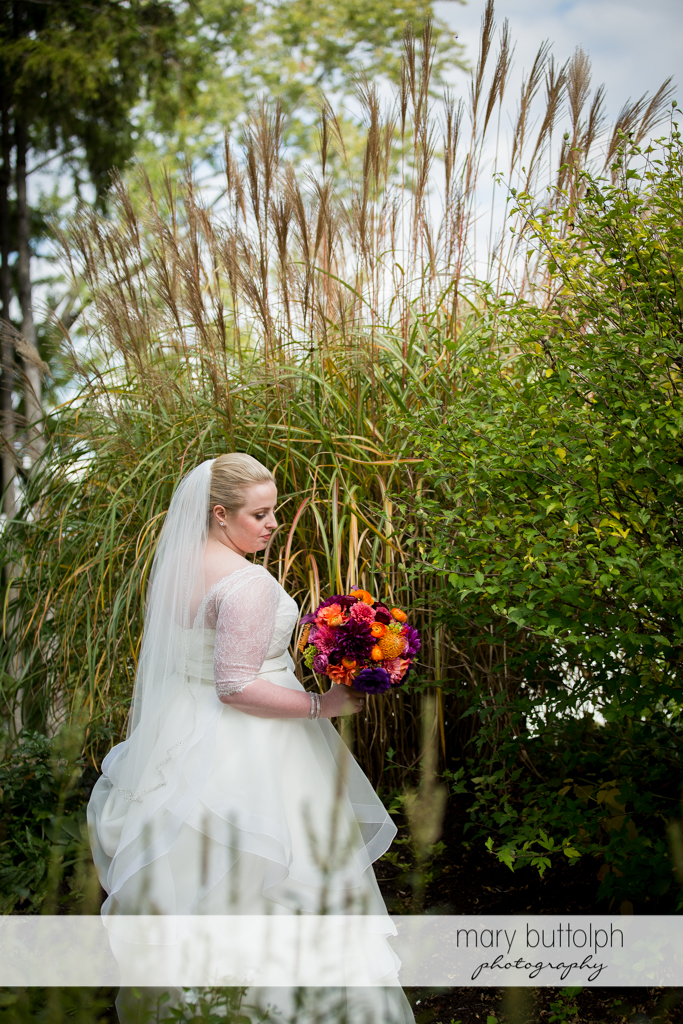 Bride with bouquet spends time in the garden at Skaneateles Country Club Wedding