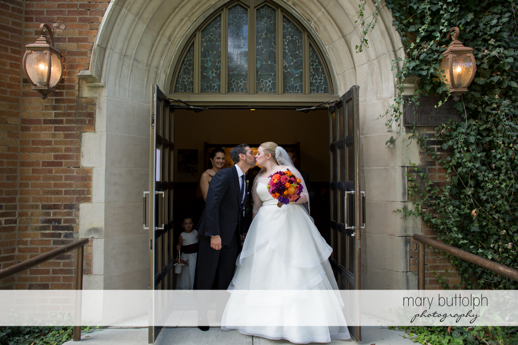 Couple kiss as they leave the church at Skaneateles Country Club Wedding