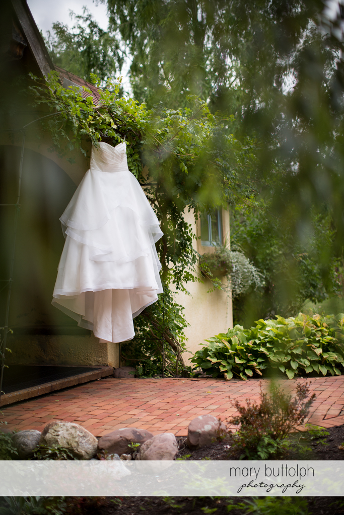 Bride's wedding gown hangs from the roof of a house at Skaneateles Country Club Wedding