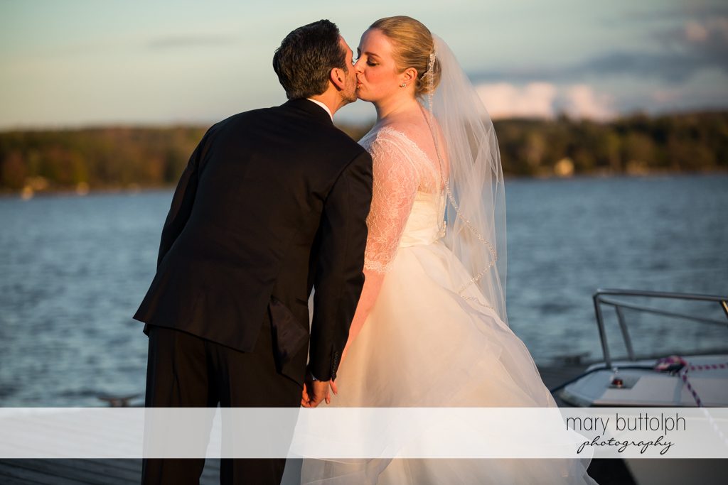 Couple kiss by the lake at Skaneateles Country Club Wedding