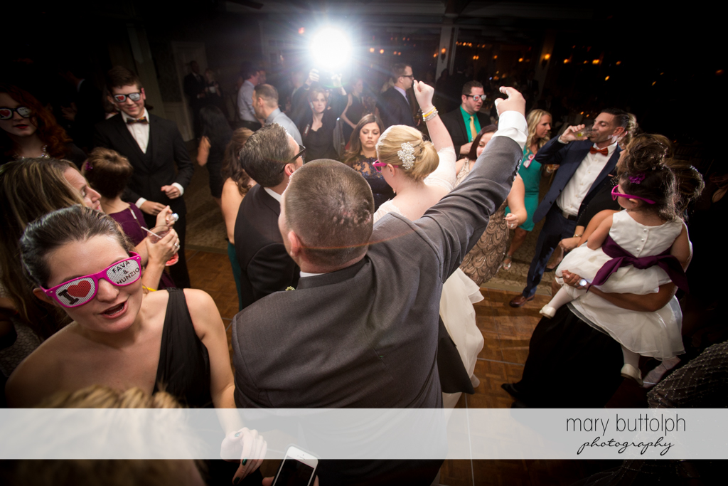 Guests wearing glasses dance at the wedding venue at Skaneateles Country Club Wedding