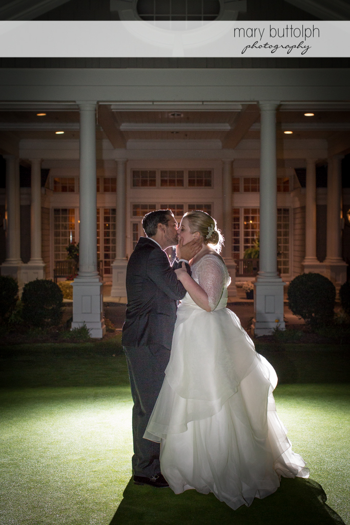 Couple kiss in front of the wedding venue at Skaneateles Country Club Wedding