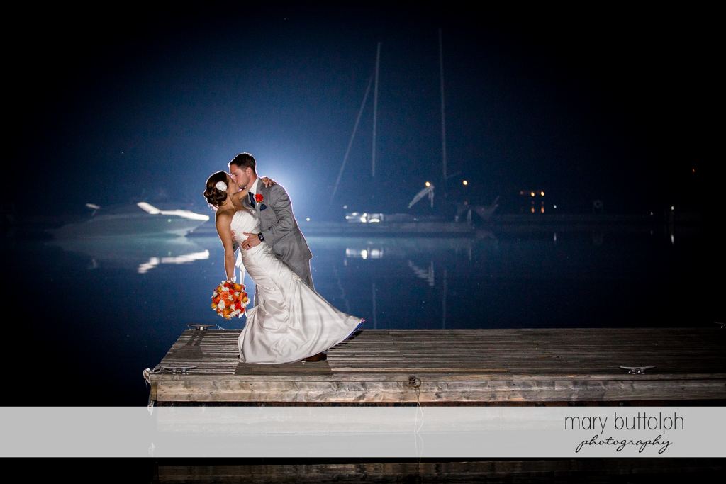 Couple kiss in the moonlight by the lake at Skaneateles Country Club Wedding