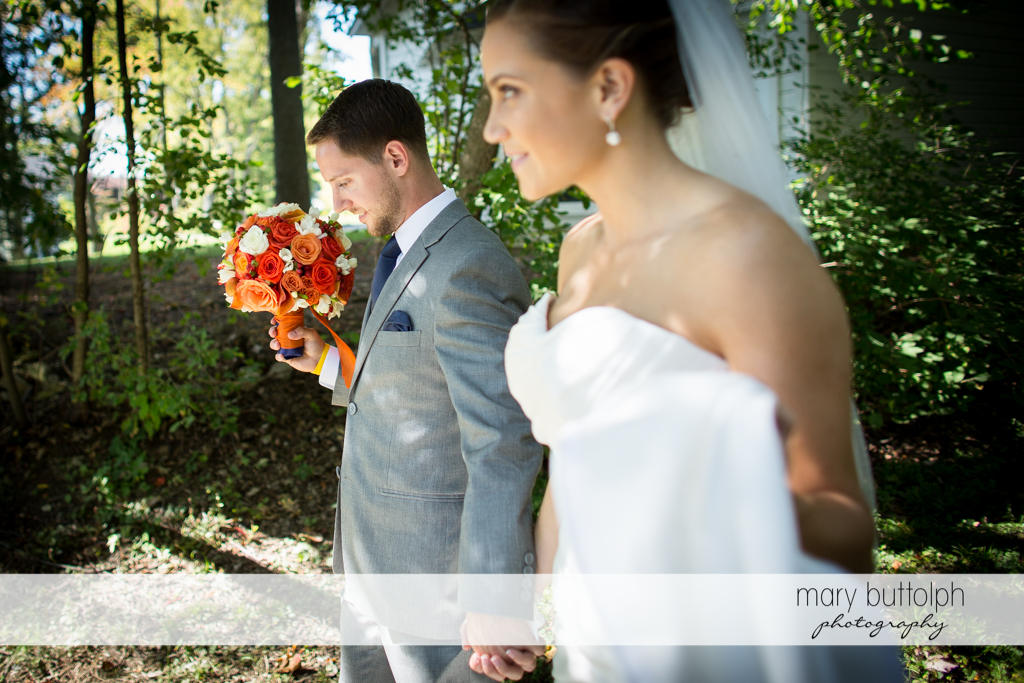 Couple hold hands in the garden at Skaneateles Country Club Wedding
