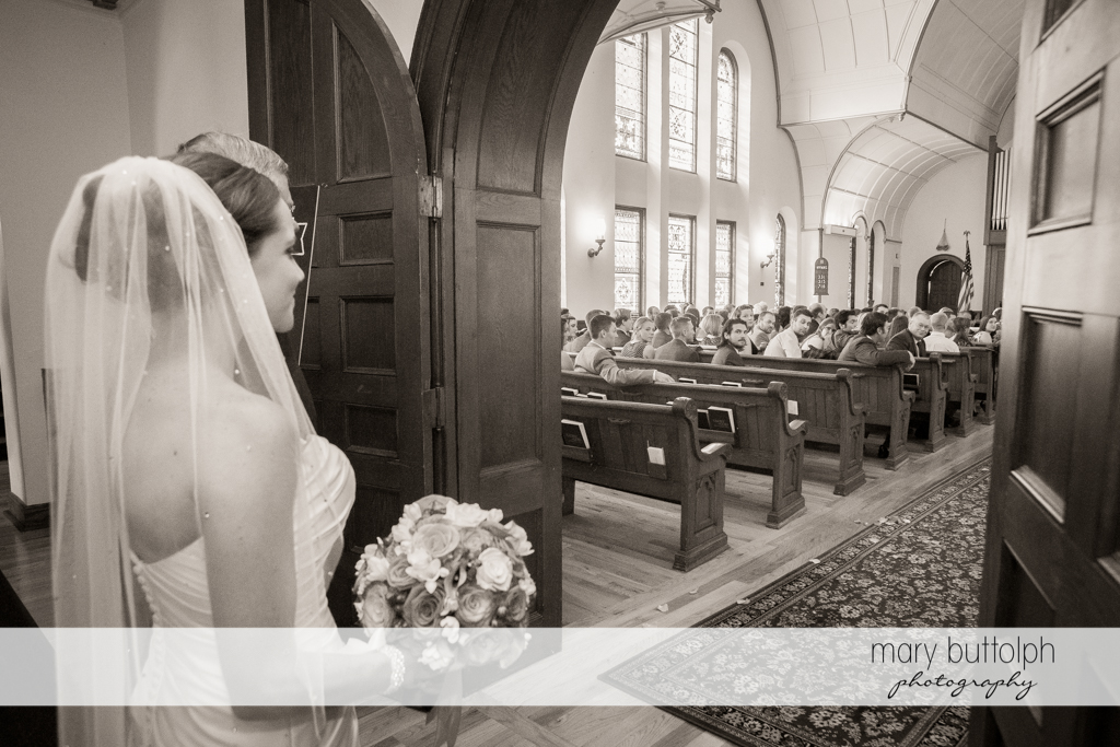 Bride with bouquet prepares to enter the church filled with guests at Skaneateles Country Club Wedding