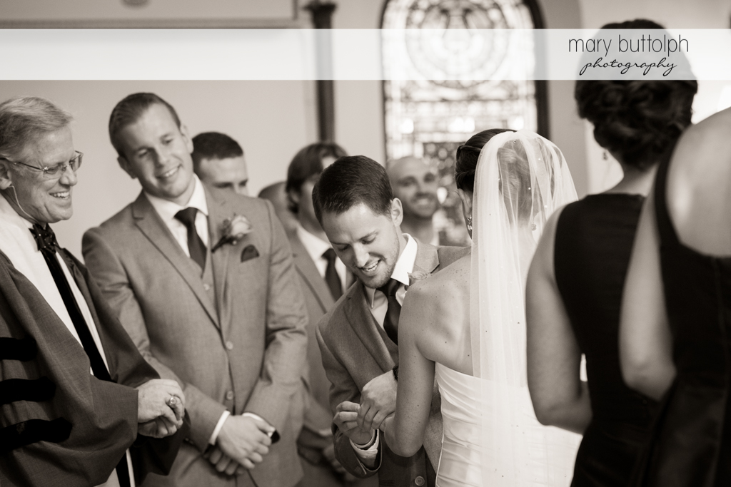 Groom slips on the bride's wedding ring as the priest and groomsman look on at Skaneateles Country Club Wedding