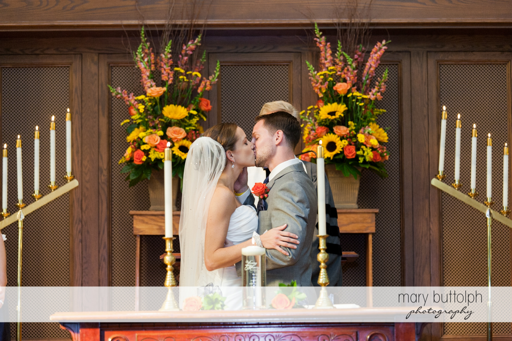Couple kiss in front of the altar at Skaneateles Country Club Wedding