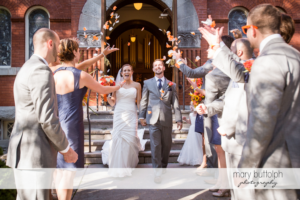 Couple are showered with flowers by the wedding party at Skaneateles Country Club Wedding