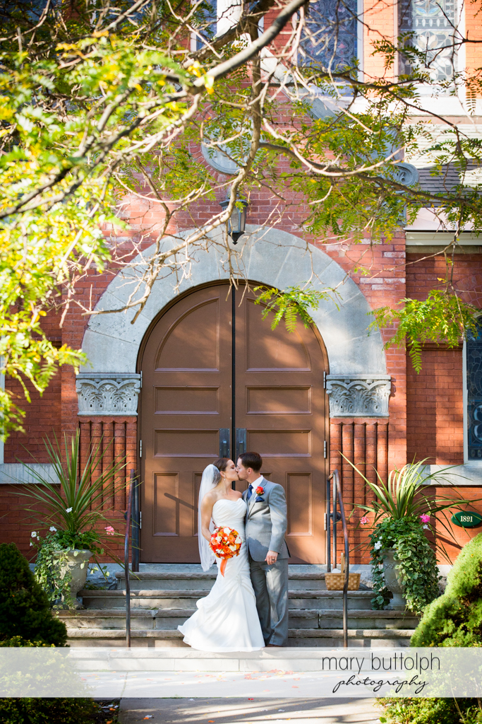Couple kiss in front of the church at Skaneateles Country Club Wedding