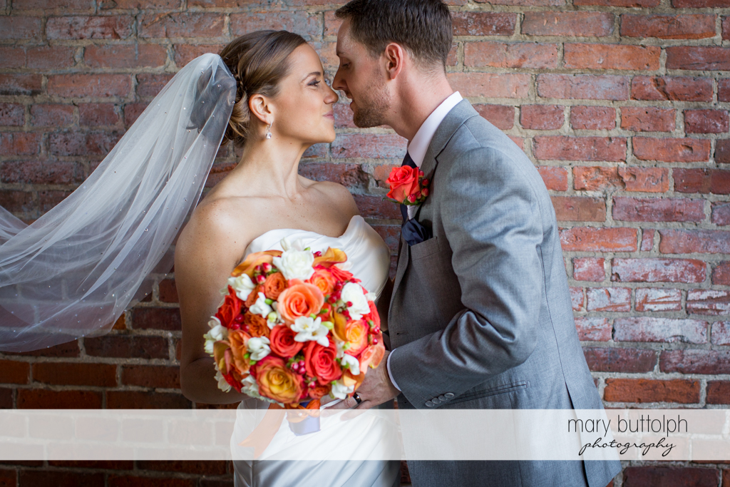 Couple share a romantic moment in front of a brick wall at Skaneateles Country Club Wedding