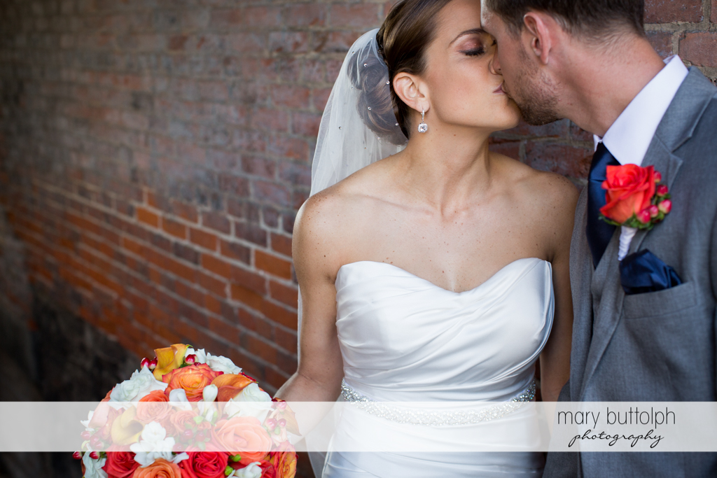 Couple kiss in front of a brick wall at Skaneateles Country Club Wedding