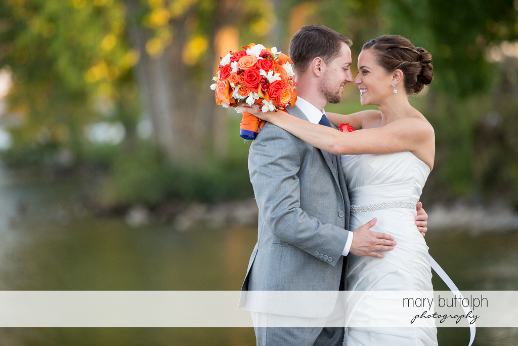 Couple embrace in the garden at Skaneateles Country Club Wedding