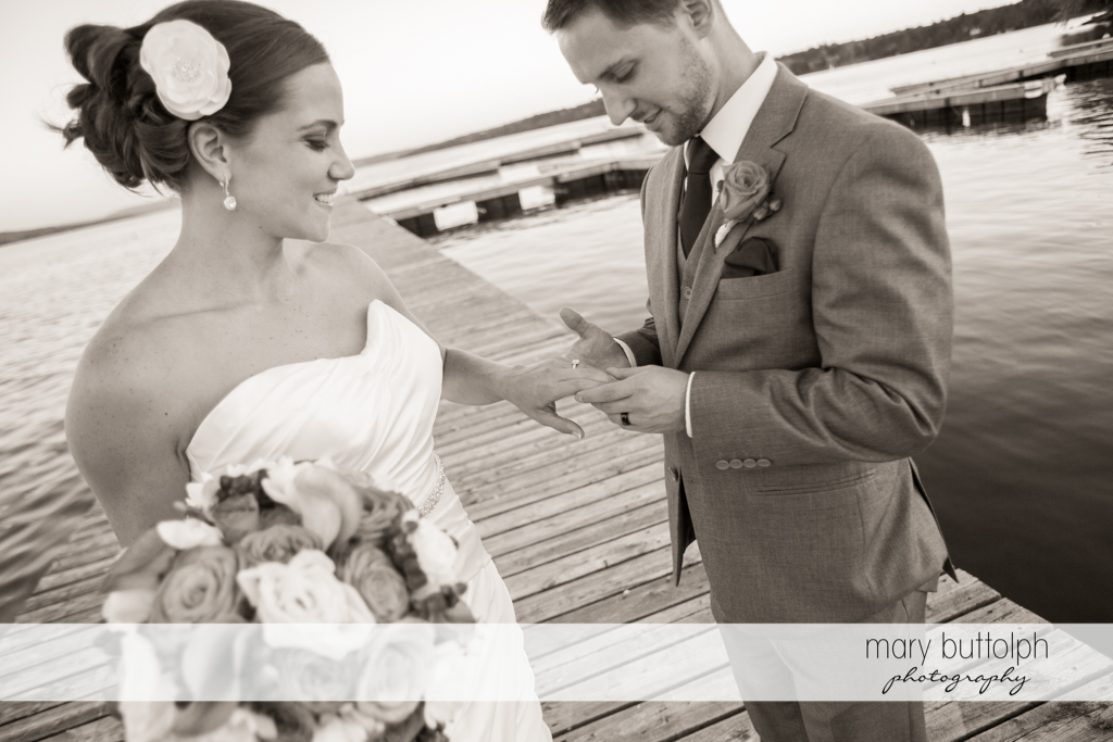 Groom looks at the bride's wedding ring on the docks at Skaneateles Country Club Wedding