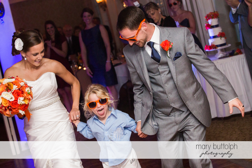 Couple with a young girl wearing sunglasses at the wedding venue at Skaneateles Country Club Wedding