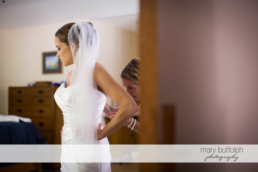 A friend adjusts the bride's wedding gown at Skaneateles Country Club Wedding