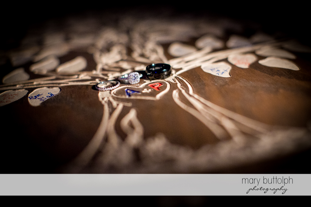 Couple's wedding rings on top of a wooden board with their initials at Skaneateles Country Club Wedding
