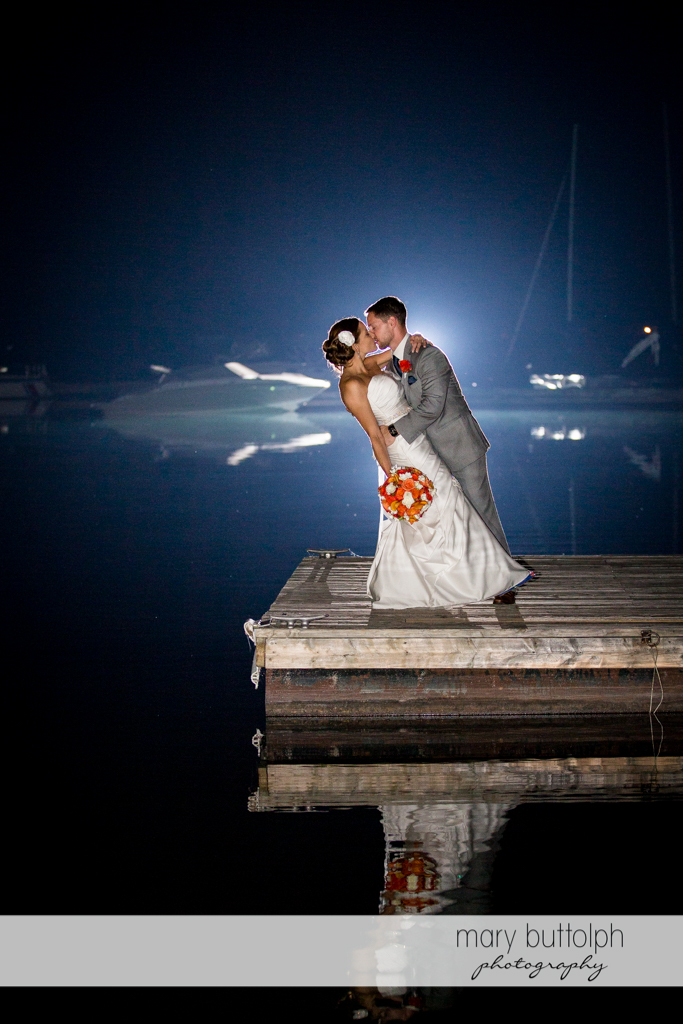Couple kiss in the moonlight on the docks at Skaneateles Country Club Wedding