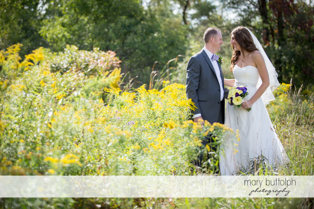 Couple stop to enjoy the wild flowers at the Sherwood Inn Wedding