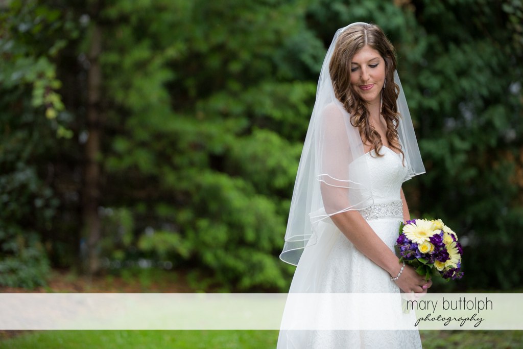 Bride with bouquet poses in the garden at the Sherwood Inn Wedding