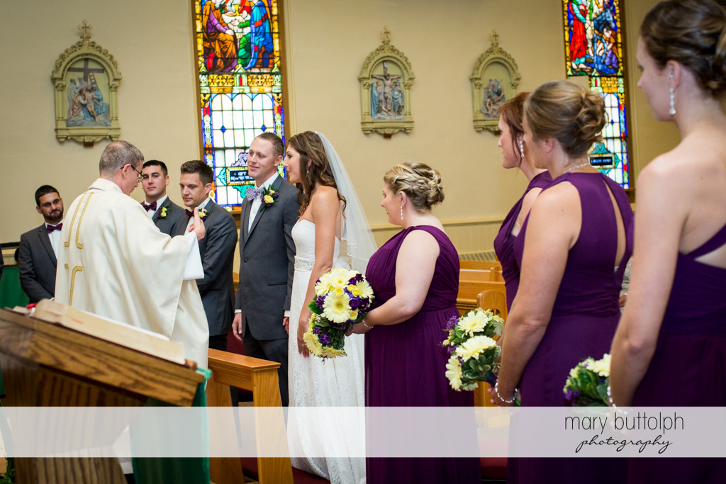 The wedding party face the priest in front of the altar at the Sherwood Inn Wedding