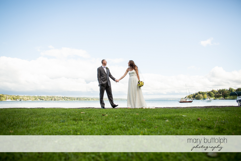 Couple hold hands in front of the lake at the Sherwood Inn Wedding
