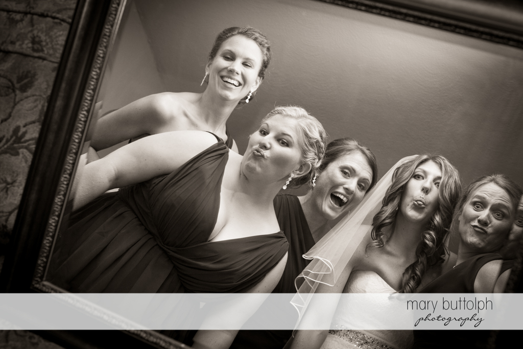 Bride and her bridesmaids clown around in front of the mirror at the Sherwood Inn Wedding