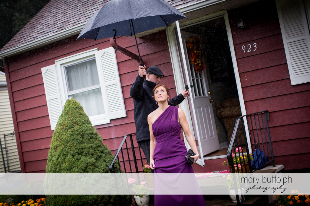 A man holds an umbrella over a bridesmaid as she steps out in the rain at the Sherwood Inn Wedding