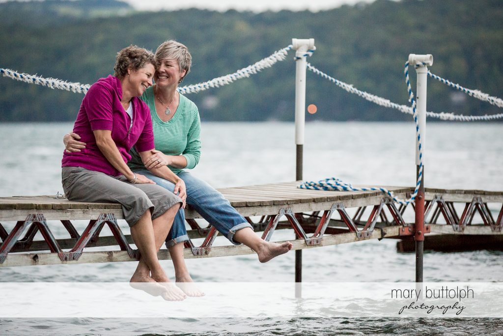 Same sex couple relax by the lake at Skaneateles Lake Engagement
