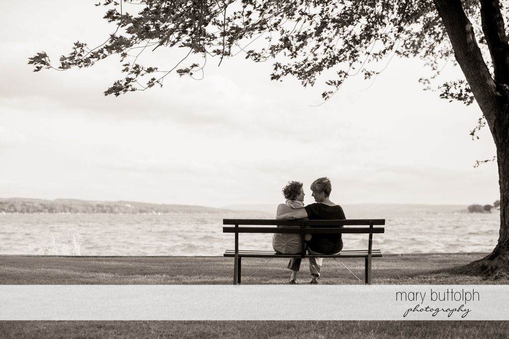 Same sex couple sit on a bench facing the lake at Skaneateles Lake Engagement