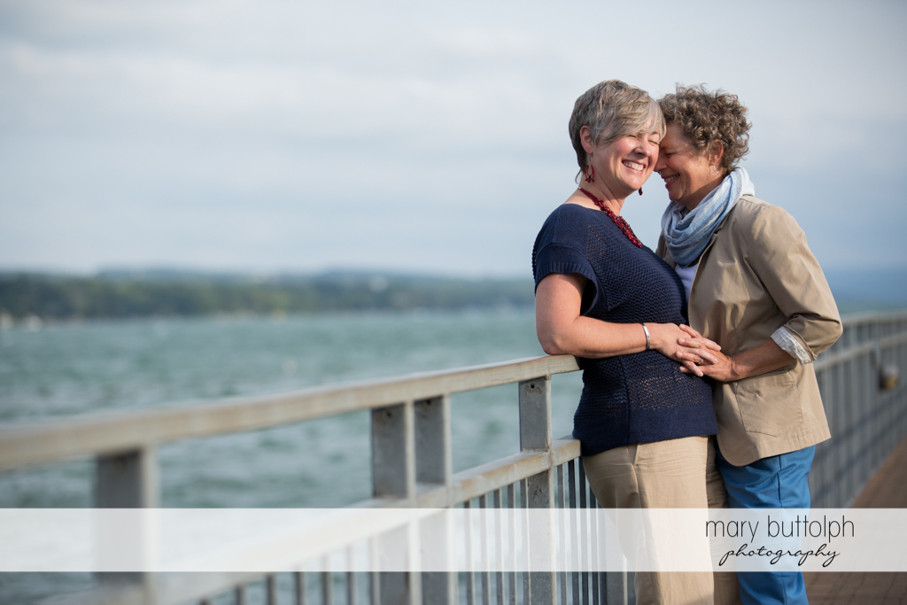 Same sex couple enjoy the lakeside view at Skaneateles Lake Engagement