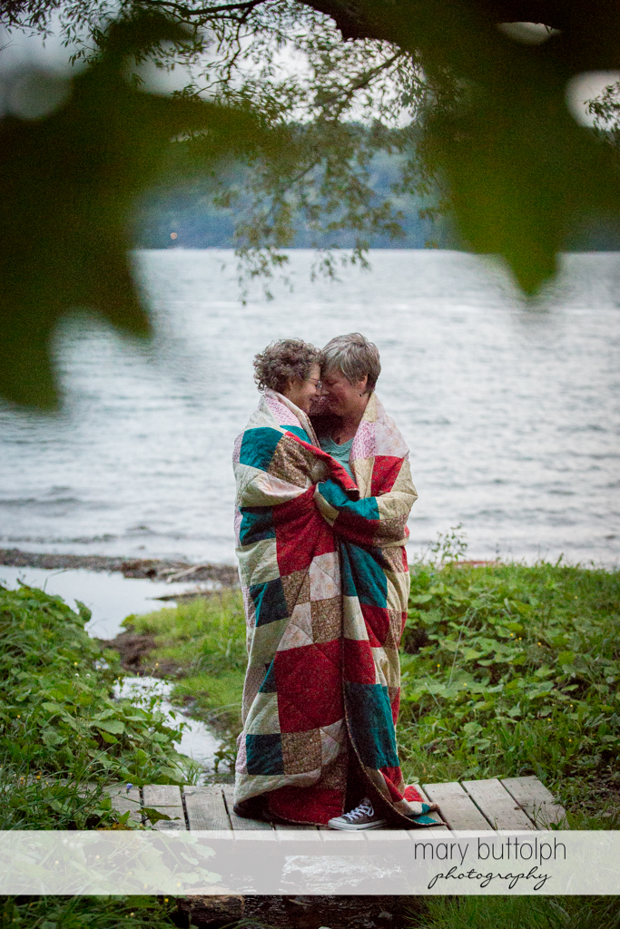 Same sex couple keep warm during the photo shoot at Skaneateles Lake Engagement