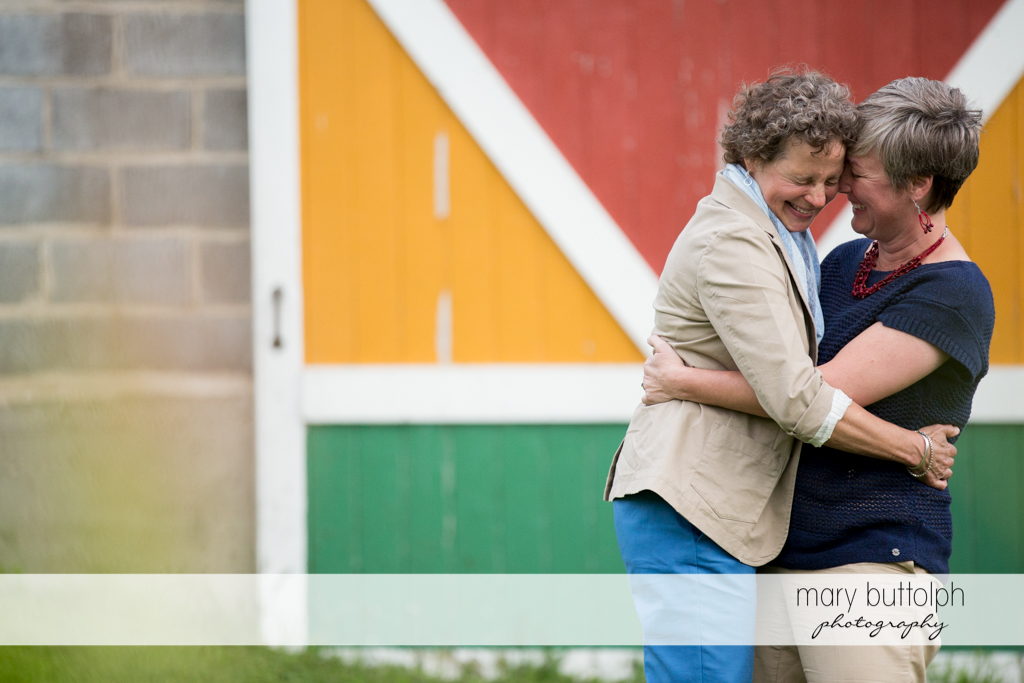 Same sex couple share a happy moment in front of a wooden door at Skaneateles Lake Engagement
