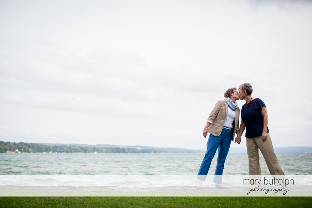 Same sex couple kiss in front of the lake at Skaneateles Lake Engagement