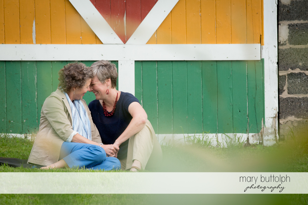 Same sex couple sit in front of a wooden door at Skaneateles Lake Engagement