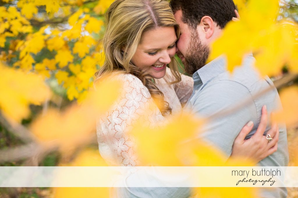 Couple show their affection in the garden at Beak & Skiff Apple Orchards Engagement