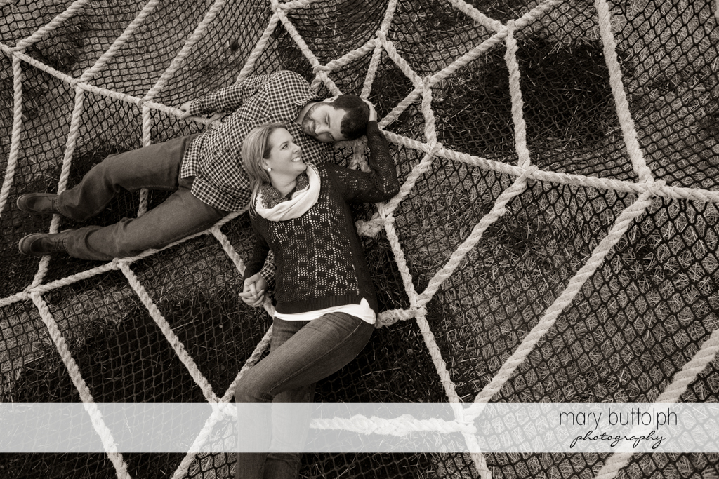 Couple lie in a large web-like hammock at Beak & Skiff Apple Orchards Engagement