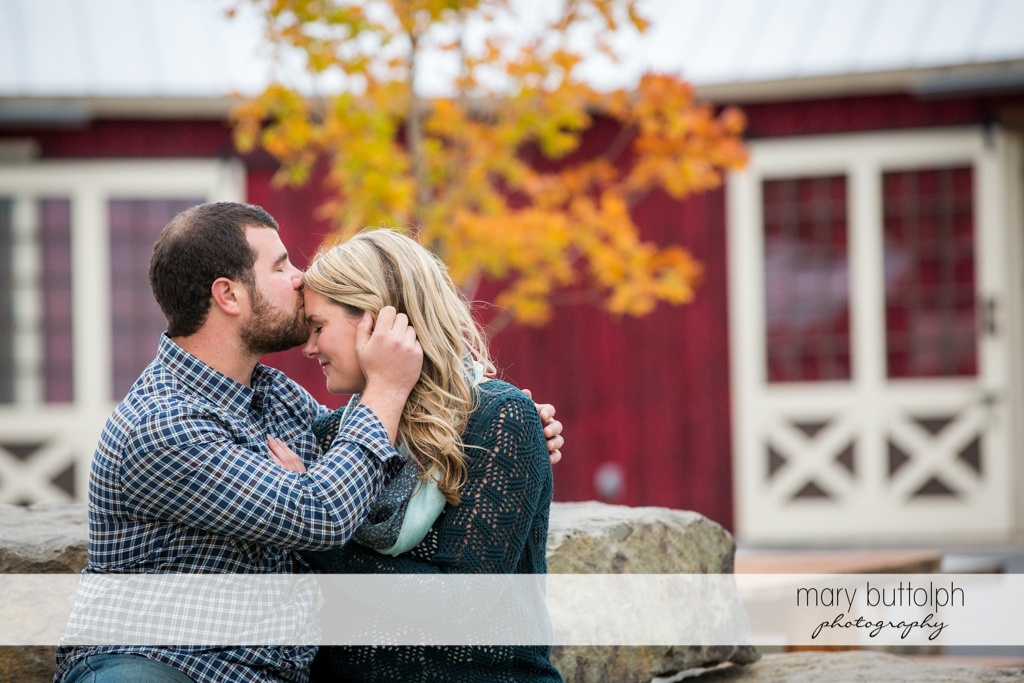 Couple spend time together in front of an old house at Beak & Skiff Apple Orchards Engagement