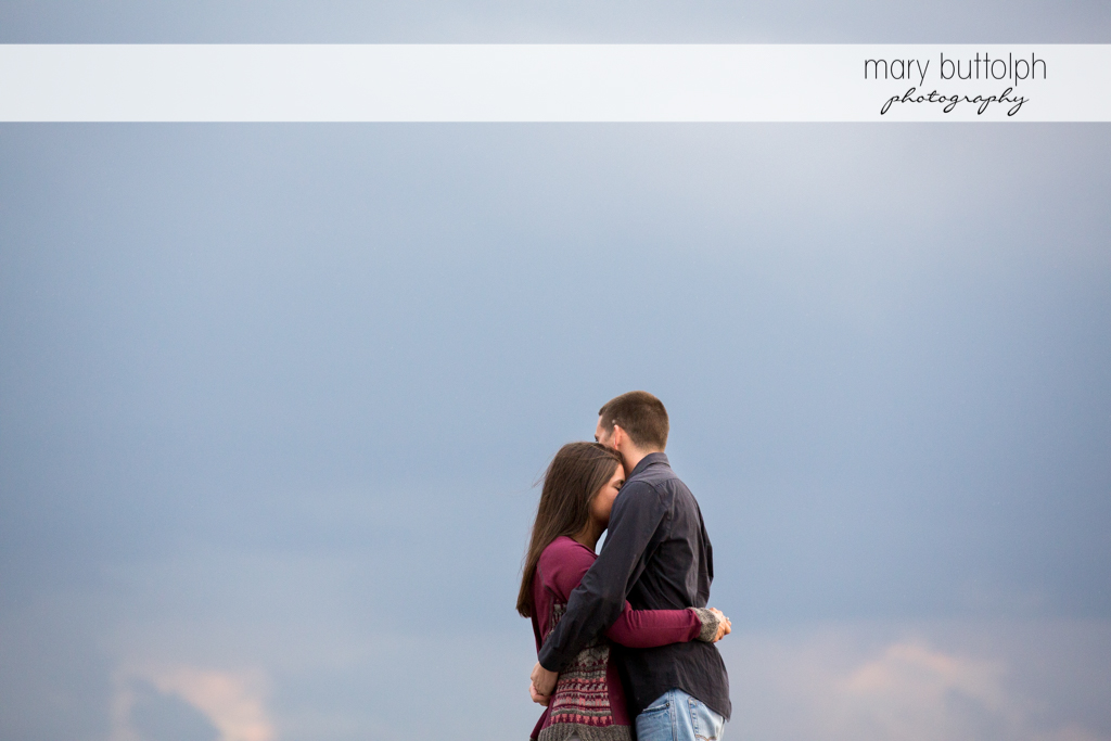 Couple embrace under the clear sky at Skaneateles Lake Engagement