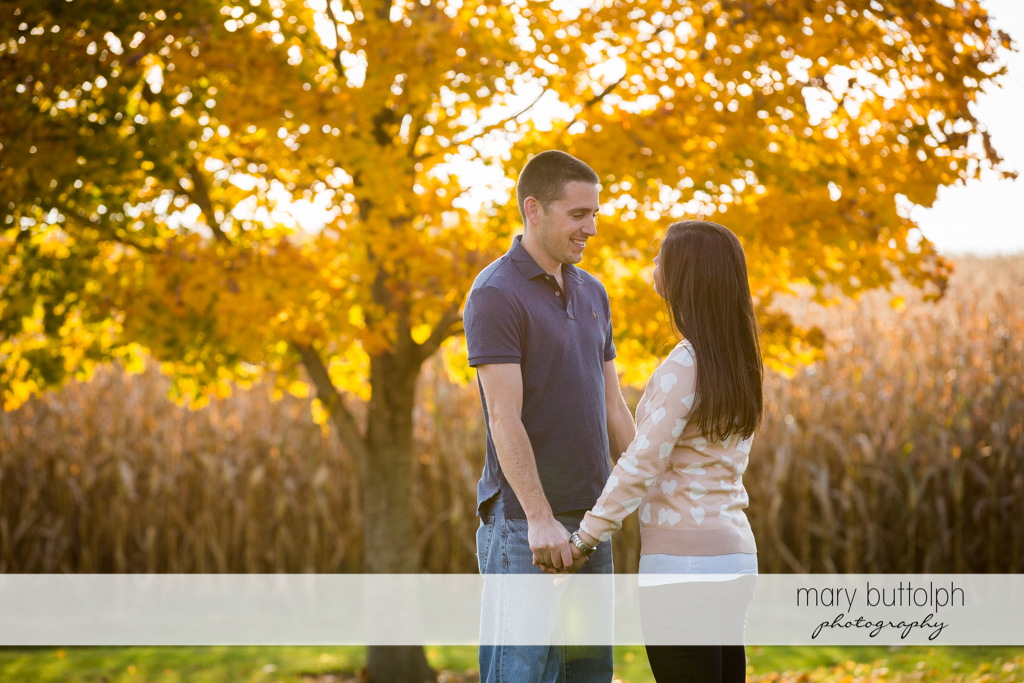 Couple hold hands in front of a tree in the garden at Skaneateles Lake Engagement