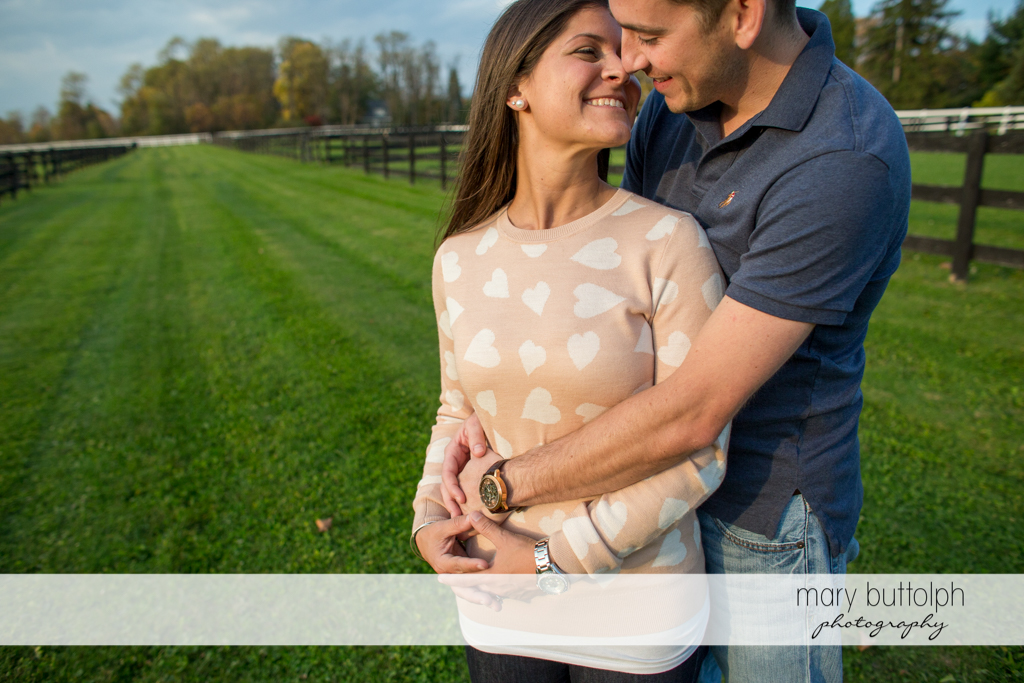 Couple share an intimate moment on the field at Skaneateles Lake Engagement