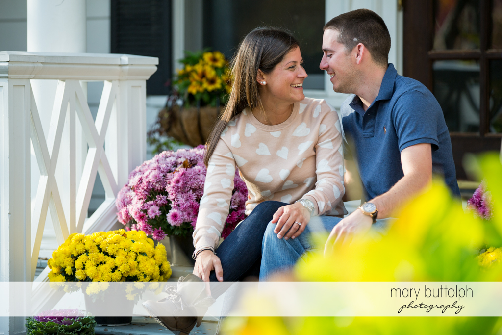 Couple sit on the porch surrounded by flowers in Skaneateles Lake Engagement