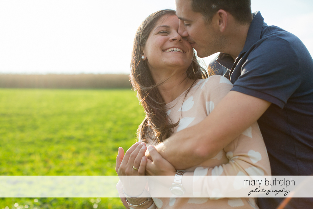Couple share a tender moment in the garden at Skaneateles Lake Engagement