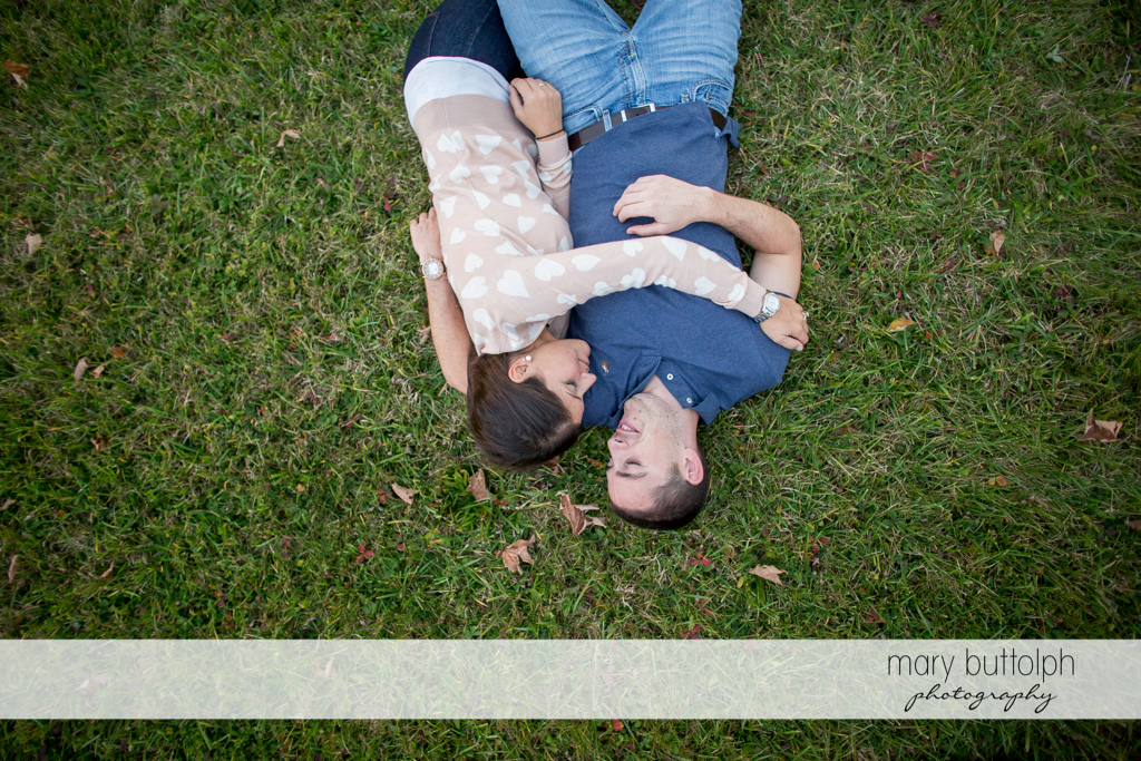 Couple lie on the grass in the garden at Skaneateles Lake Engagement