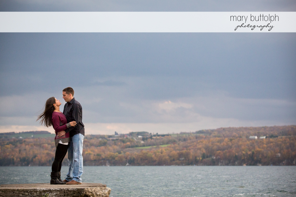 Couple embrace by the lake at Skaneateles Lake Engagement