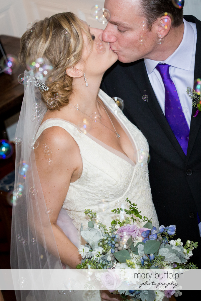 Couple kiss as bubbles fall on them at Rowland House Wedding