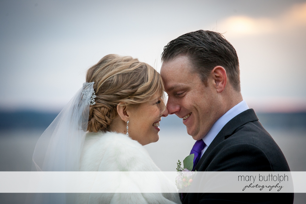 Couple rub noses by the lake at Rowland House Wedding