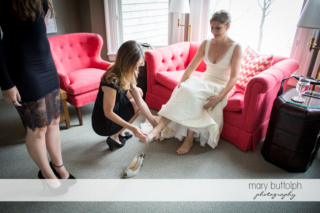 Bride wears one of her wedding shoes with the help of a friend at Rowland House Wedding