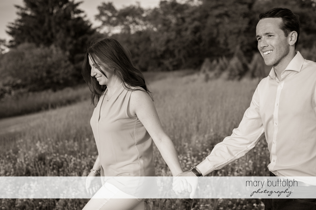 Couple hold hands as they cross the garden in Cazenovia Engagement