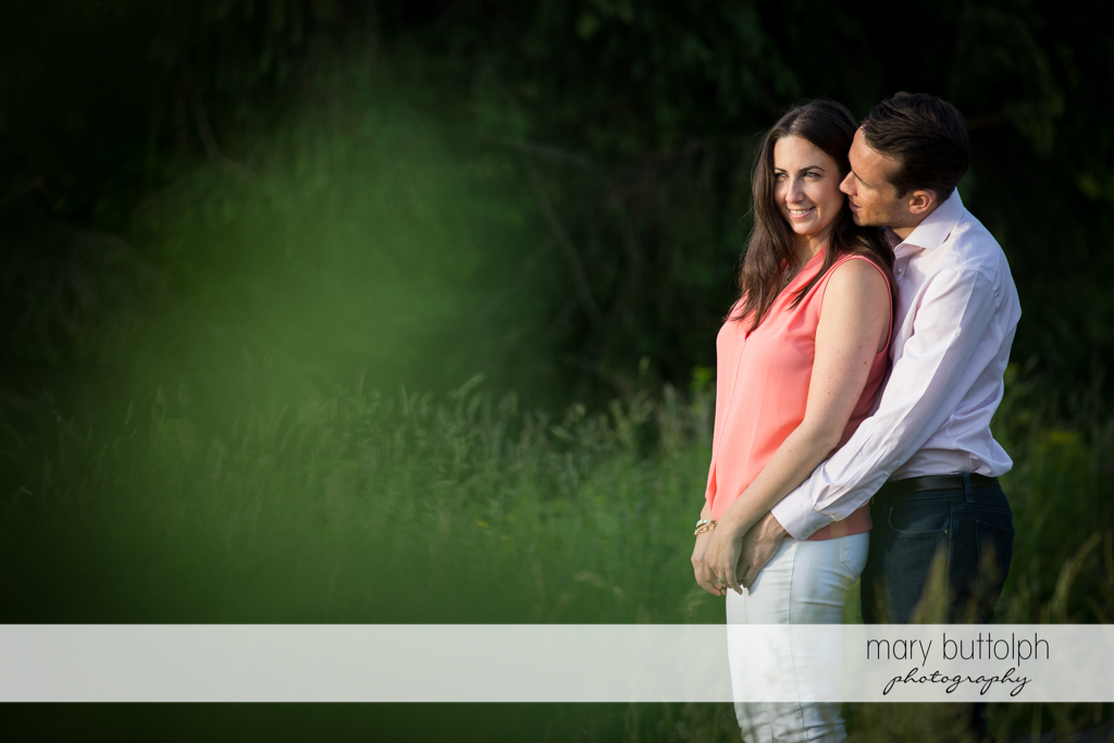 Couple cuddle up in the garden at Cazenovia Engagement